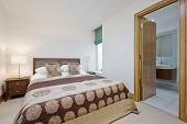 contemporary bedroom with open door to en-suite bathroom