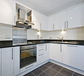 modern white kitchen with black granite worktop