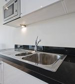 stainless steel kitchen sink on black granite worktop