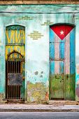 Old shabby house in Havana with a cuban flag painted on its door and the words Viva Cuba poster