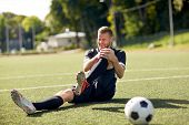 sport, football training, sports injury and people - injured soccer player with ball on field poster