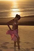 beautiful  bikini dressed with a saron young brazilian  woman in jericoacoara at the sunset ceara st