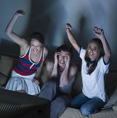 pictures in a living room of two young girls and a man sitting on a couch  watching on tv  sport eve