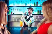 Barkeeper smiling while preparing cocktail for female customers at bar counter poster