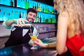 Barkeeper serving cocktail to young woman at counter in nightclub poster