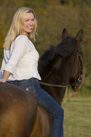 pic of bareback  - An attractive young woman riding a horse bareback during the fall - JPG