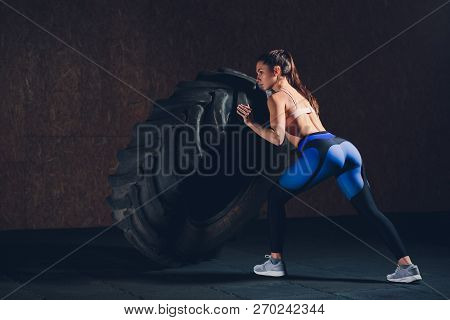 poster of Fitness Woman Flipping Wheel Tire In Gym. Fit Female Athlete Working Out With A Huge Tire. Back View