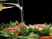 Pouring olive oil and fresh salad.