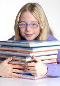 School girl portrait behind books.
