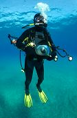 Underwater photographer with big camera and flashes.