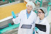 High Angle  Portrait Of Two Female Factory Workers Standing By Macaroni Conveyor Belt And Looking Up poster