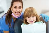 Female dentist and child in a dentist office poster