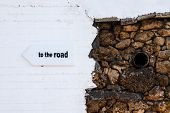 to The Road Sign On An Arrow Pointing Direction. On A Contrasting Wall. poster