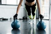 Cropped View Of Fit Sportswoman In Weightlifting Gloves Doing Plank Exercise On Kettlebells At Gym poster