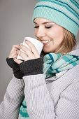 Pretty winter teenage girl holding mug with hot beverage