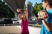 Smiling mature couple stretching after exercise outdoors on city street. Happy fitness woman doing s poster