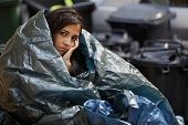 poor homeless young woman wrapped in plastic tarpaulin.