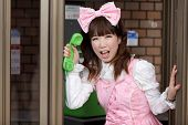 japanese girl in sweet lolita cosplay style in public phone, Tokyo