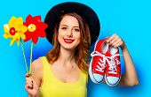 Portrait Of Young Smiling Red-haired White European Woman In Hat With Pinwheels Toy And Red Gumshoes poster