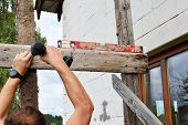 Worker Hands Screwing Screw In Wooden Board With Cordless Screwdriver Outdoors Next To White Unfinis poster