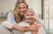Cheerful mature woman embracing senior mother at home and looking at camera. Portrait of elderly mot poster