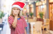 Young beautiful girl wearing christmas hat over isolated background looking stressed and nervous wit poster
