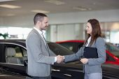 Businesswoman shaking hand of a man in a dealership