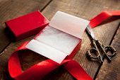Opening or preparing a gift in a red box.  A red gift box, scissors, and a red ribbon. Focus is in t