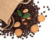 Coffee beans in a hessian drawstring sack and loose with amaretto biscuits, almond nuts and leaf spr