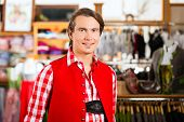 Traditional clothes - young man is buying Tracht or lederhosen in a shop, he has to try it on before