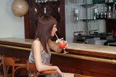 pic of single woman  - Beautiful woman drinking cocktail near the bar counter - JPG