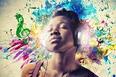 image of treble clef  - Black girl listening to the music with a pair of headphones - JPG