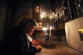 JERUSALEM - OCTOBER 01: Pilgrims pray at the tomb of Jesus in the Church of the Holy Sepulchre, trad