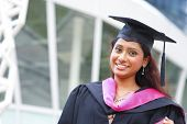 Stock image of Indian female graduate student standing in front school building