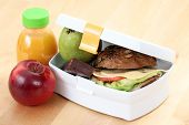 stock photo of lunch box  - box with sandwich fruits and chocolate and bottle of juice - JPG