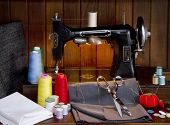 Retro sewing machine with sewing paraphernalia including thread, fabric, sewing needles, pin cushion