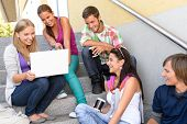 Students having fun with laptop school stairs teens college laughing