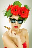 sexy young woman wearing sunglasses and red gerbera flowers on her head holding a cigar in her hands and looking to the camera - vintage picture style