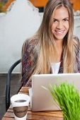 Portrait of a beautiful young woman with long hair using laptop at cafe