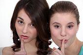 Two female friends shushing.