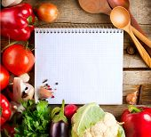 Fresh Organic Vegetables and Spices on a Wooden Background and Paper for Notes. Open Notebook and Fr