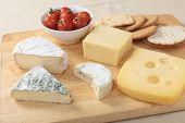 A cheeseboard with Jarlsberg, Cheddar, herbed Brie, Camembert and St Albry cheeses, a bowl of cherry tomatoes and some biscuits