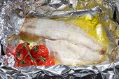 A white fish fillet and a sprig of cherry tomatoes baked with butter in aluminium foil.