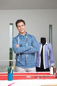 pic of cross-dresser  - Portrait of young male tailor standing arms crossed with mannequin in background - JPG