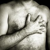 Black and white image of a topless man suffering a pain in his chest