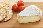 A wedge of St Albray cheese with crackers and cherry tomatoes on a cheeseboard