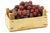 fresh red seedless grapes on the vine in a wooden crate on a white background
