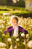 picture of hay fever  - Girl sitting in a meadow with dandelions and has hay fever or allergy - JPG
