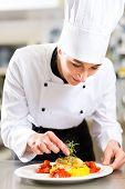 Weiblich-Chef im Hotel oder Restaurant Küche kochen, sie ist ein Gericht auf Teller beenden