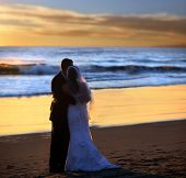stock photo of wedding couple  - Couple wedding on the beach at sunset - JPG